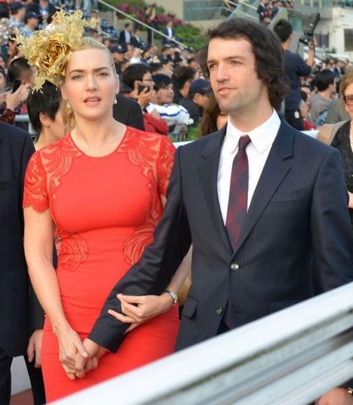 Kate winslet dans robe rouge tient la main de Ned en costume